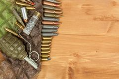 Different types of ammunition on a wooden background. Grenade and bullets. Arms trade royalty free stock photography