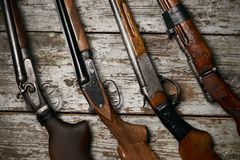 Different types of ancient hunting shotguns. On wooden background. Collection of hunting rifles, close-up Stock Photography