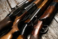 Different types of ancient hunting shotguns. On wooden background. Collection of hunting rifles, close-up Stock Images