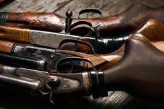 Different types of ancient hunting shotguns. On wooden background. Collection of hunting rifles, close-up Royalty Free Stock Image