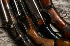 Different types of ancient hunting shotguns. On wooden background. Collection of hunting rifles, close-up Stock Photo