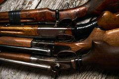 Different types of ancient hunting shotguns. On wooden background. Collection of hunting rifles, close-up Royalty Free Stock Photos