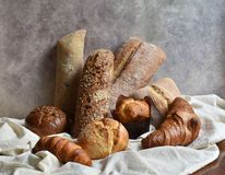 Different types of baking still life. Buns croissants, muffins and loaves, bread patties on textile drapery. Rustic. Style vintage bakery poster. Rural pastry royalty free stock photo