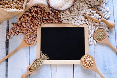 Different types of beans around black framed square on blue wood Royalty Free Stock Photography