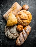 Different types of bread. On dark rustic background royalty free stock image