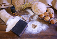 Different types of bread, fruit cakes and scattered flour on woo Royalty Free Stock Photos