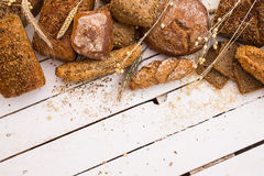 Different types of bread on white wooden board Stock Images