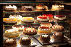 Different types of cakes in pastry shop glass display Stock Image