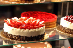 Different types of cakes in pastry shop glass display Royalty Free Stock Photo