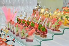 Different types of canapes in transparent glasses and wooden skewers on a glass step support on a banquet, side view stock photos