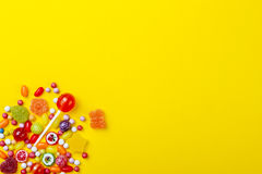 Different types of candies on yellow background, copy space. Royalty Free Stock Photo