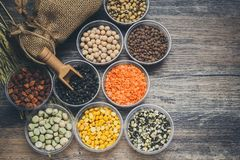 Different types of cereal beans that have a variety of nutritional benefits on the wooden floor.  royalty free stock photography