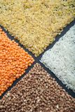 Different types of cereals and legumes chickpeas, red lentils, buckwheat, rice on a black background royalty free stock photos