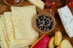 Different types of cheese, cherry tomato, spice and jam on wooden board. Close-up of different types of cheese, cherry tomato, spice and jam on wooden board Royalty Free Stock Photos