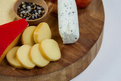 Different types of cheese, cherry tomato, spice and jam on wooden board. Close-up of different types of cheese, cherry tomato, spice and jam on wooden board Royalty Free Stock Photography