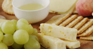 Different types of cheese with crispy biscuits, fruits and sauce. On wooden board stock footage