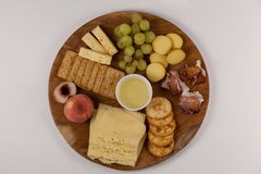 Different types of cheese, crispy biscuits, fruits and sauce on wooden board. Against white background Stock Photo