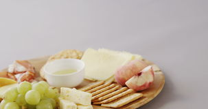 Different types of cheese, crispy biscuits, fruits and sauce on wooden board. Against white background stock footage