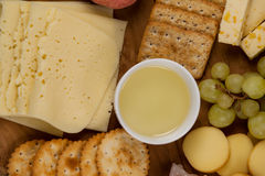 Different types of cheese, crispy biscuits, fruits and sauce on wooden board. Close-up of different types of cheese, crispy biscuits, fruits and sauce on wooden Stock Images