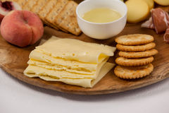 Different types of cheese, crispy biscuits, fruits and sauce on wooden board. Close-up of different types of cheese, crispy biscuits, fruits and sauce on wooden Royalty Free Stock Image