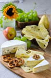 Different types of cheese with fruits and nuts. Cheese, pears, grapes, nuts and pretzels on wooden cutting board Stock Images
