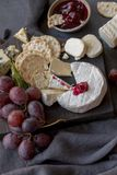 Different types of cheese with grape on wood board stock images