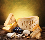 Different types of cheese on old wood. Different types of cheese over old wooden table royalty free stock photography