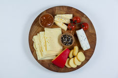 Different types of cheese, tomatoes and bowl of jam. On wooden board Royalty Free Stock Image