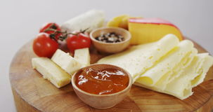 Different types of cheese, tomatoes and bowl of jam. On wooden board stock video footage