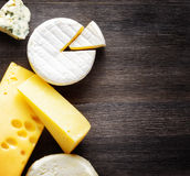 Different types of cheese on a wooden board Stock Photos