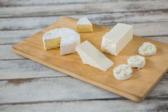 Different types of cheese. On wooden board against grey background Stock Photography