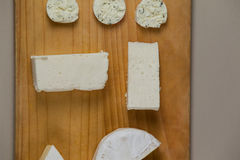 Different types of cheese. On wooden board against grey background Royalty Free Stock Photos