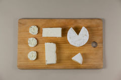 Different types of cheese. On wooden board against grey background Royalty Free Stock Photo