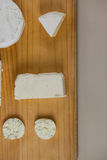 Different types of cheese. On wooden board against grey background Stock Photos