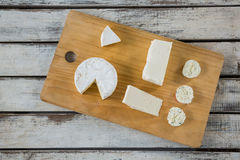 Different types of cheese. On wooden board against grey background Stock Images