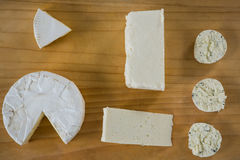 Different types of cheese. On wooden board against grey background Royalty Free Stock Image