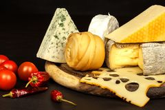 Different types of cheeses with tomato and chili pepper on the kitchen board. Preparation of healthy food. Different types of cheeses with tomato and chili stock image