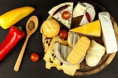 Different types of cheeses with tomato and chili pepper on the kitchen board. Preparation of healthy food. Different types of cheeses with tomato and chili Royalty Free Stock Photos