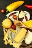 Different types of cheeses with tomato and chili pepper on the kitchen board. Preparation of healthy food. Different types of cheeses with tomato and chili Stock Photos