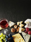 Different types of cheeses with wine glass and fruits. Stock Photos