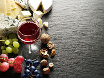 Different types of cheeses with wine glass and fruits. Royalty Free Stock Photos