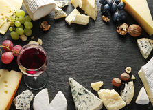 Different types of cheeses with wine glass and fruits. Stock Photography