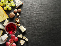 Different types of cheeses with wine glass and fruits. Royalty Free Stock Photography