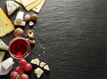 Different types of cheeses with wine glass and fruits. Royalty Free Stock Images