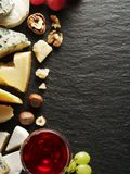 Different types of cheeses with wine glass and fruits. Stock Photo
