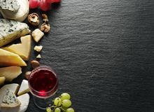 Different types of cheeses with wine glass and fruits. Royalty Free Stock Image