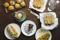 Different types of coffee and food on dark table, top view stock photo