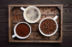 Different types of coffee - ground, grain and beverage on dark wooden background
