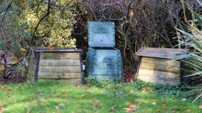 Different types of composter in a garden. Different types of composter in wood or plastic in a garden Stock Images