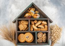 Different types of cookies: cereal, kantuchini, Chinese and puff, in a wooden box in the shape of a house stock photos